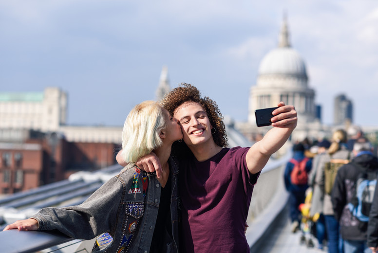 Happy couple taking a selfie photograph on Londons Millennium Bridge