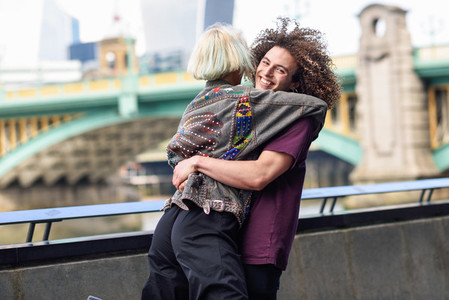 Happy couple hugging near the Southwark bridge over River Thames London