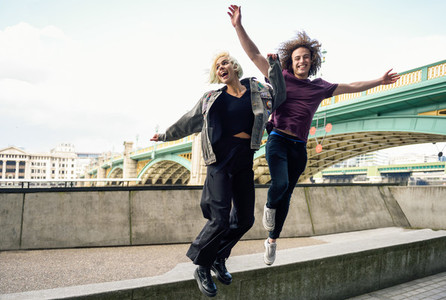 Funny couple junping near the Southwark bridge over River Thames London