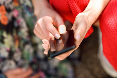 Woman hands touching touch screen of a smart phone outdoors