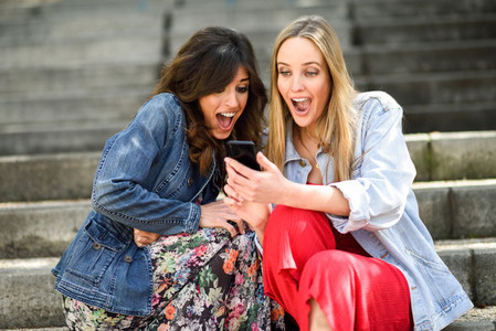 Two young women looking some awesome thing on their smart phone