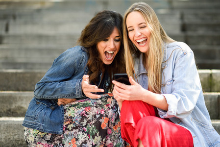 Two girls looking at some funny thing on their smart phone