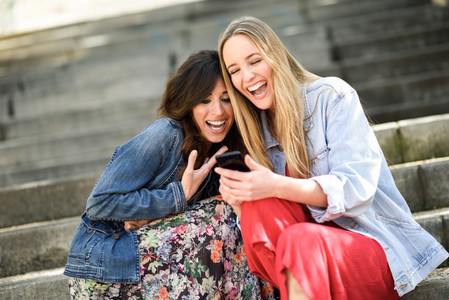 Two women looking at some funny thing on their smart phone
