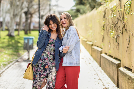 Two happy young women friends hugging in the street