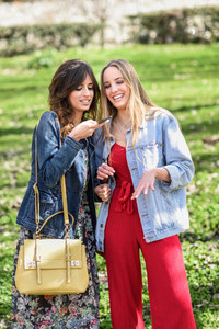 Two young women using the voice recognition of the phone outdoor