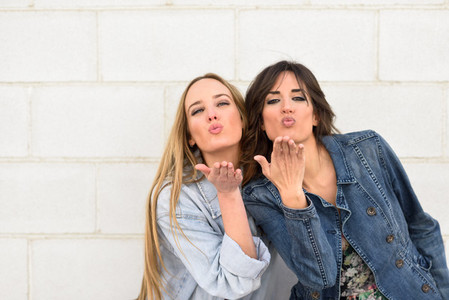 Two young women blowing a kiss on urban wall