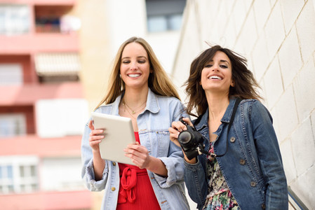 Two young tourist women looking maps with digital tablet outdoor