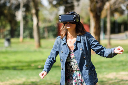 Woman looking in VR glasses and gesturing with his hands outdoor