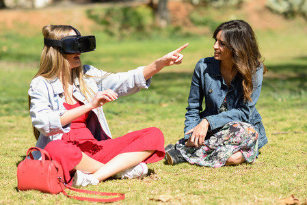 Two women looking in VR glasses and gesturing with his hands out