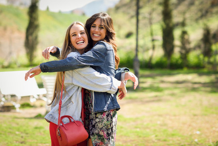 Two happy young women friends hugging in urban park