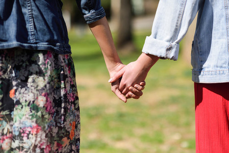 Two young women in walking holding her hands in urban park
