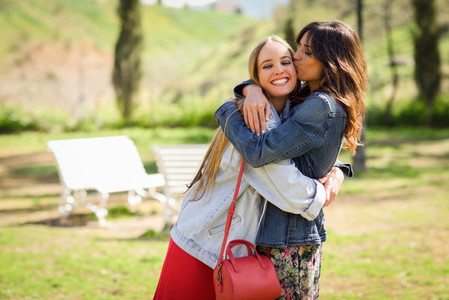 Young woman kissing her friend face outdoors