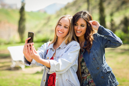 Two young women taking a selfie photograph in urban park