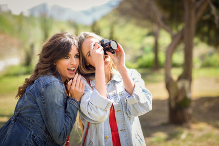 Two young tourist women taking photographs outdoors