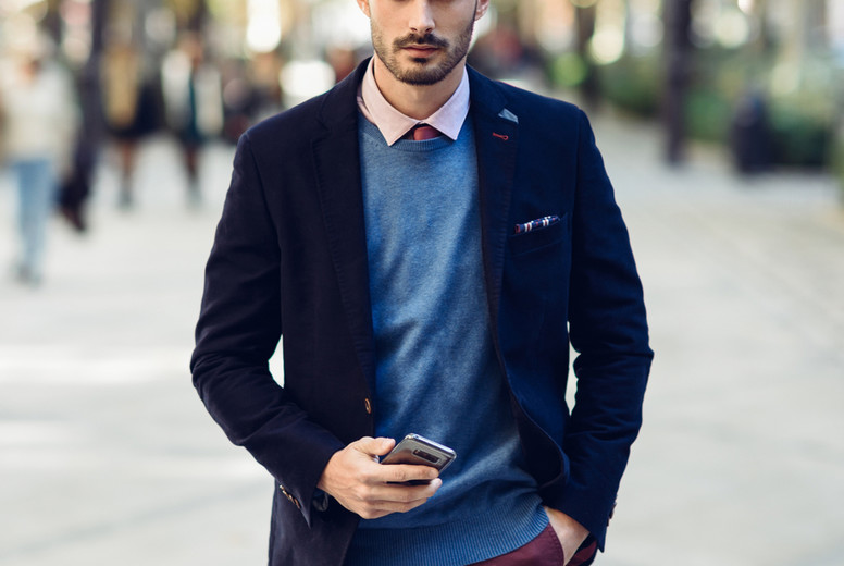 Man in the street in formalwear with smartphone in his hand