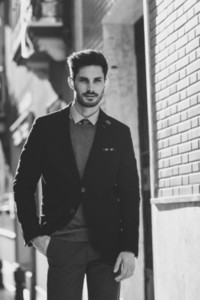 Attractive man wearing british elegant suit in the street Modern hairstyle