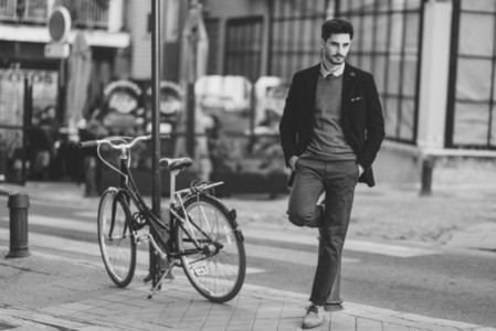 Man wearing british elegant suit in the street near an old bycicle