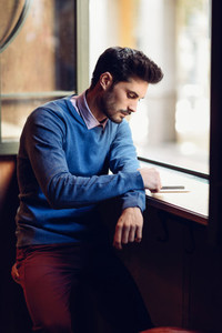 Young man with blue sweater looking at his smartphone in a moder