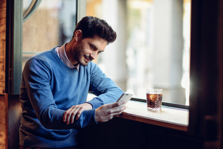 Smiling man with blue sweater looking at his smartphone in a mod