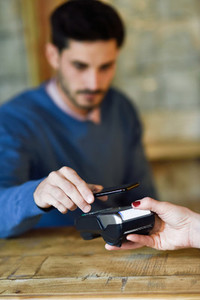 Hand holding smartphone paying on EDC machine