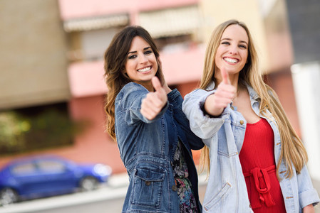 Two young women with thumbs up outdoors