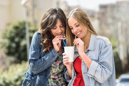 Two young women drinking the same drink with two straws
