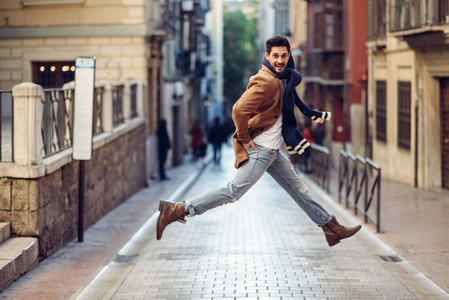 Young happy man jumping wearing winter clothes in urban backgrou