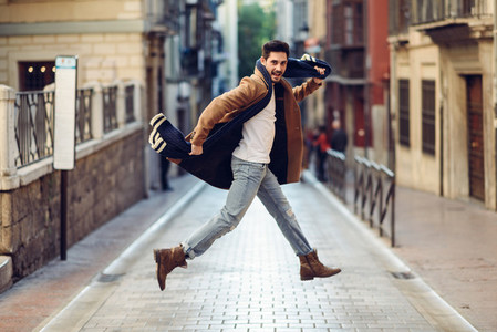 Young happy man jumping wearing winter clothes in urban background