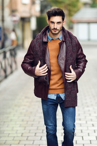 Attractive young man walking in an urban road in winter clothes