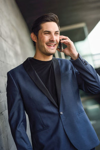 Attractive young businessman on the phone in an office building