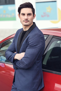 Attractive young businessman standing near a red car