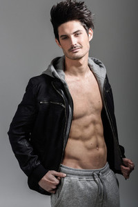Athletic man wearing hoodie jacket Studio shot