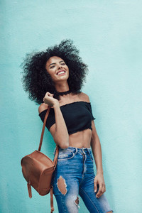 Happy mixed woman with afro hair standing on the street