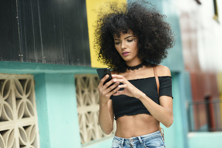 Black woman afro hair on the street holding a smartphone