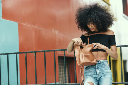 Young mixed woman looking for something in her bag