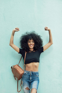 Funny black woman with afro hair raising arms outdoors