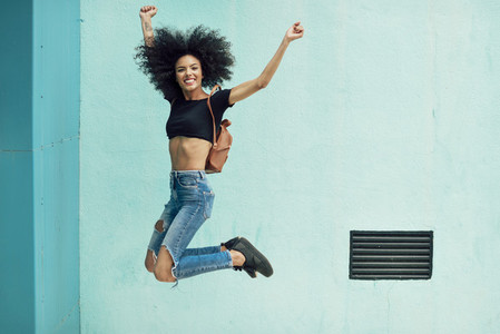 Young mixed woman with afro hair jumping outdoors