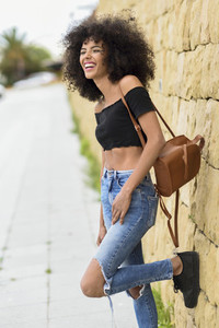 Happy mixed woman with afro hair laughing outdoors