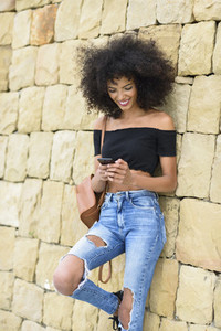 Smiling woman looking at her smart phone outdoors