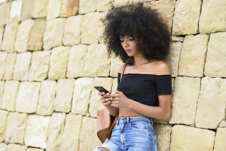 Serious black woman looking at her smart phone outdoors