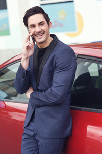 Young businessman talking with his mobile phone near a car