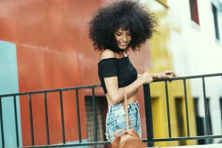 Young woman with curly hair near a modern colorful building
