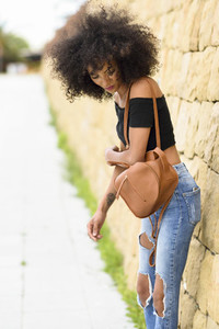 Young mixed woman with afro hair standing on the street