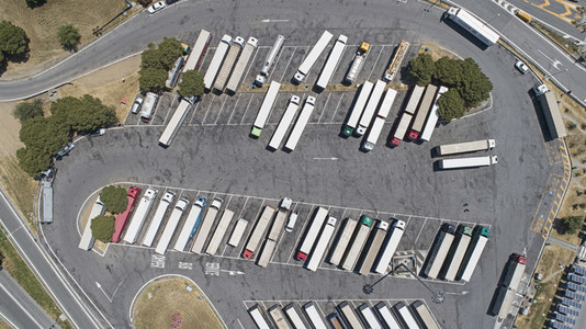 Aerial view from above semi trucks parked in sunny rest stop parking lot