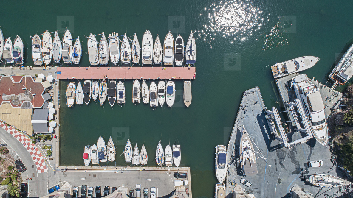 Aerial view from above sunny boats and yachts moored in harbor