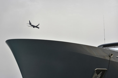 Airplane flying over ship in overcast sky