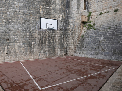 Basketball court and hoop in stone courtyard
