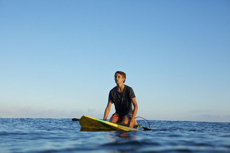 Boy kneeling on paddle board on blue ocean