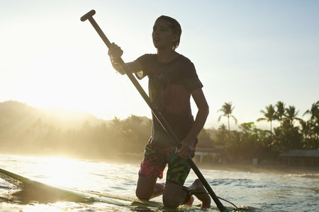 Boy kneeling on paddle board on sunny sunset ocean