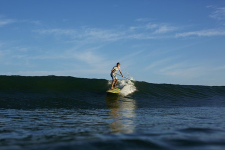 Boy paddle boarder riding sunny  blue ocean wave